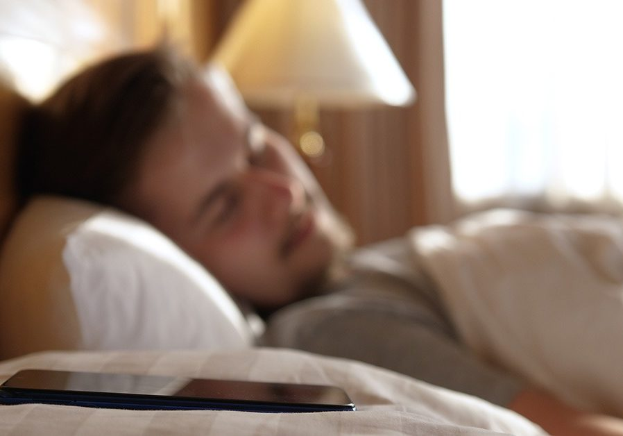 man sleeping with smart phone on pillow